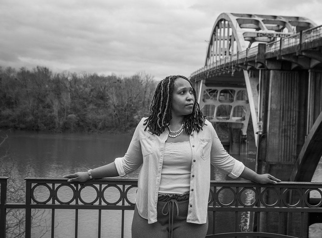 Jerria Martin black and white photo standing in front of a bridge and a river looking to the left calml
