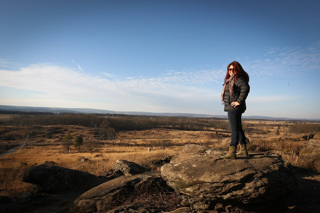 Wendie at Gettysburg standing on top of a rock with the battle field behind her