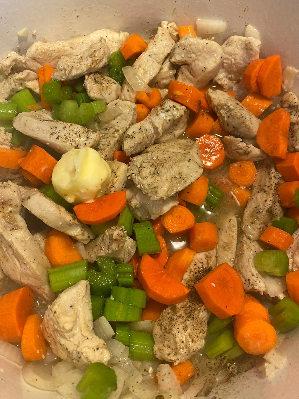 Add vegetables to cooked chicken.