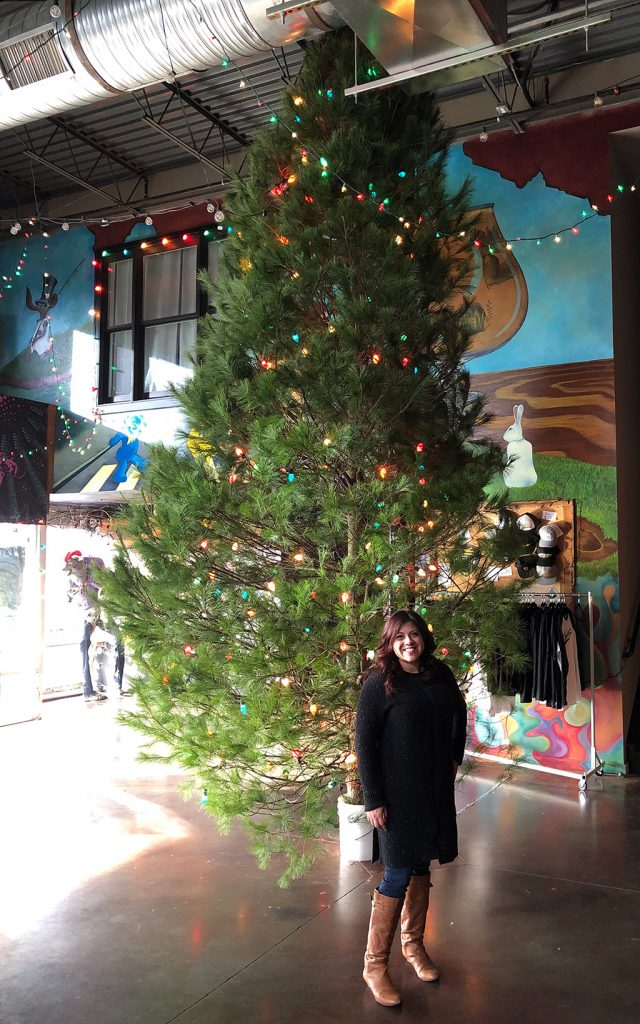 Wendie V in front of a large Christmas tree