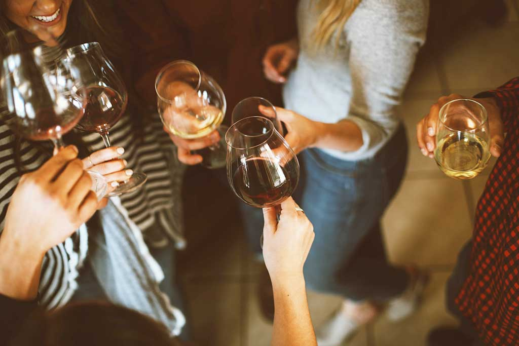 People holding white and red wine glasses toasting