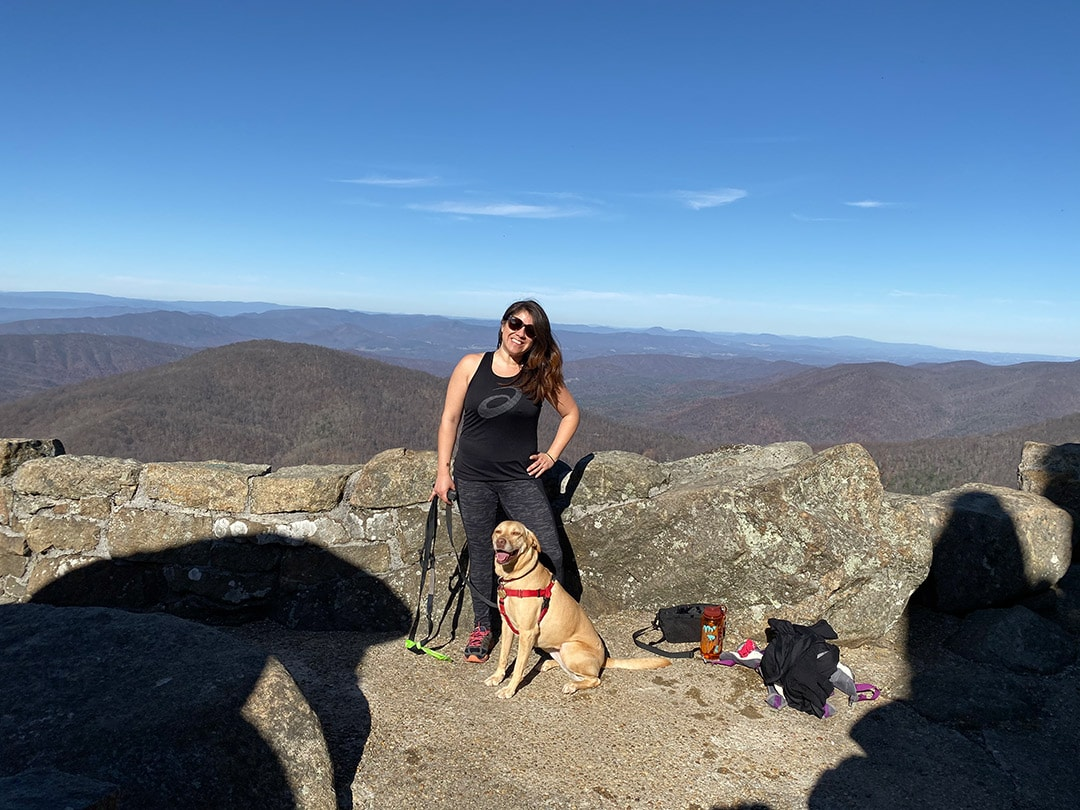 Wendie and Asha hiking in the Blue Ridge standing in front of a blue sky at the top of the mountain