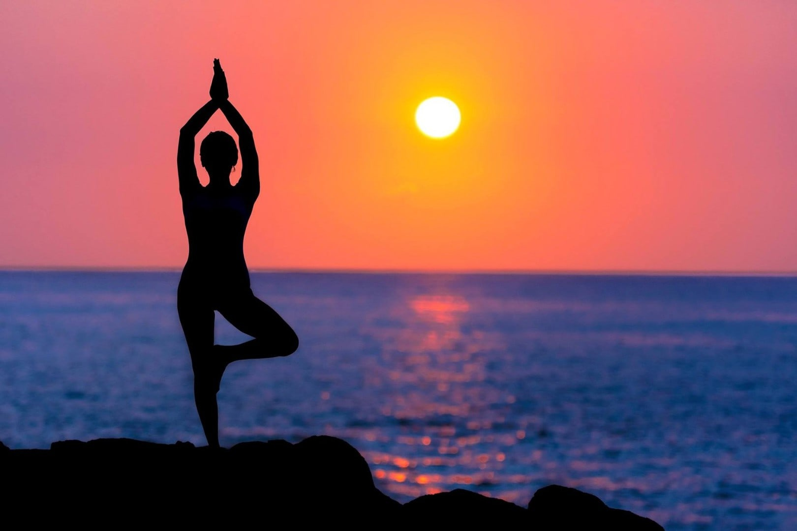 Woman standing in tree pose in front of a orange pink sunset over the ocean