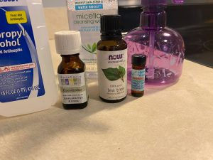 Smaller image focused on essential oil bottles. Lavender, tea tree, and eucalyptus oils are used in this recipe.