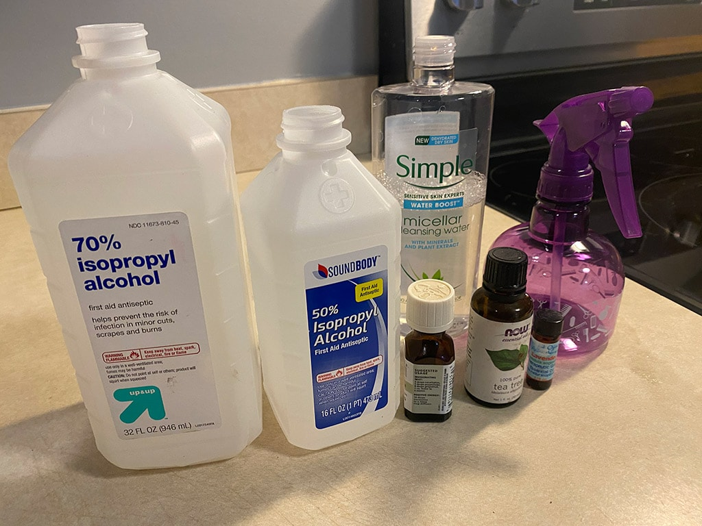 Empty purple spray bottle, essential oils, 50 and 70% isopropyl alcohol and micellar cleansing water.