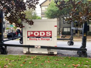 PODS container in the delivery system that moves in all directions with four wheels and large metal posts. The container is left on a street occupying 2 parking spaces.