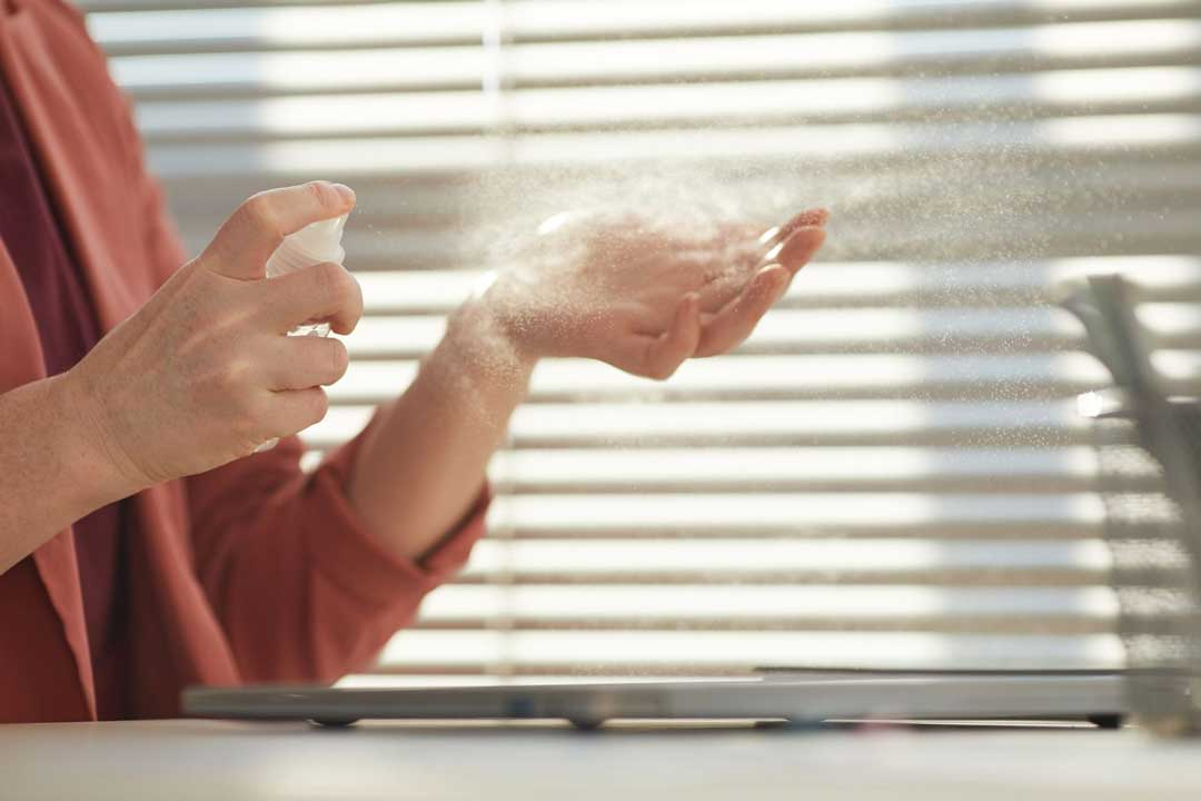Person spraying hand sanitizer on their left hand in front of a window