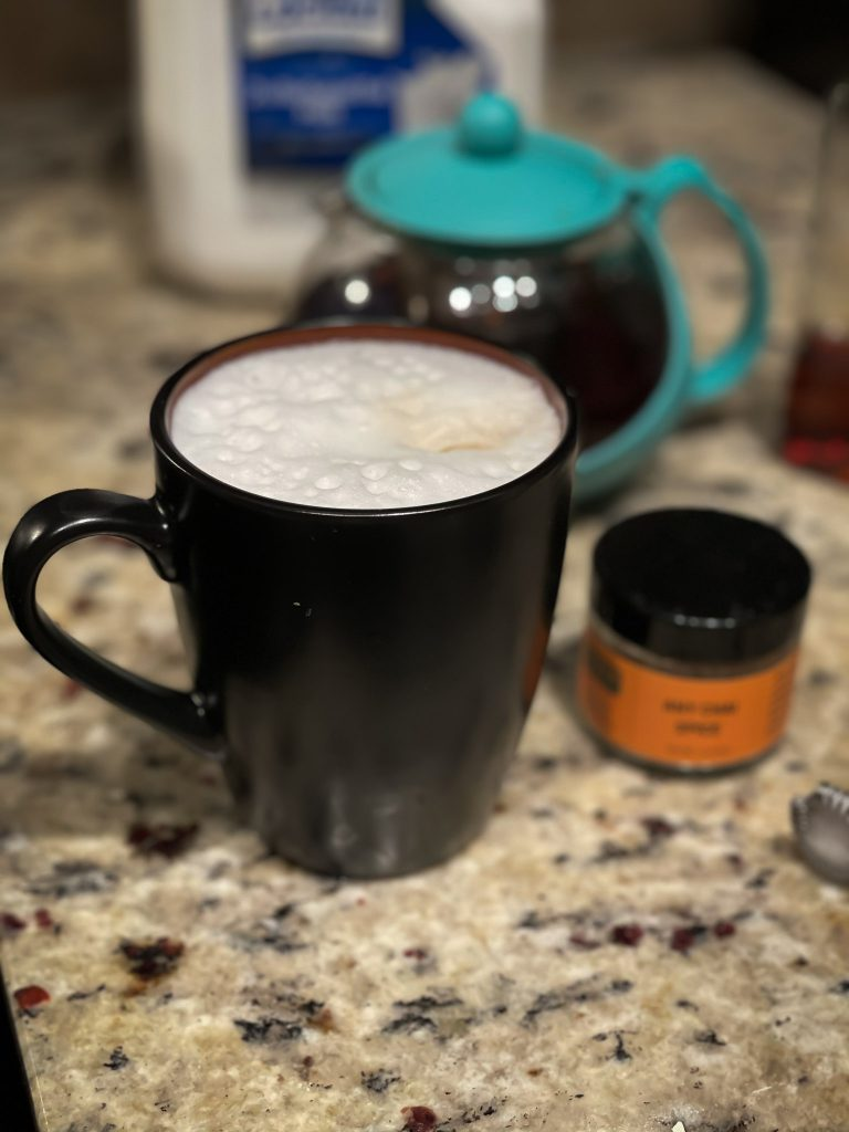 Mug of hot chai tea on a counter with chai spice and tea pot on a counter