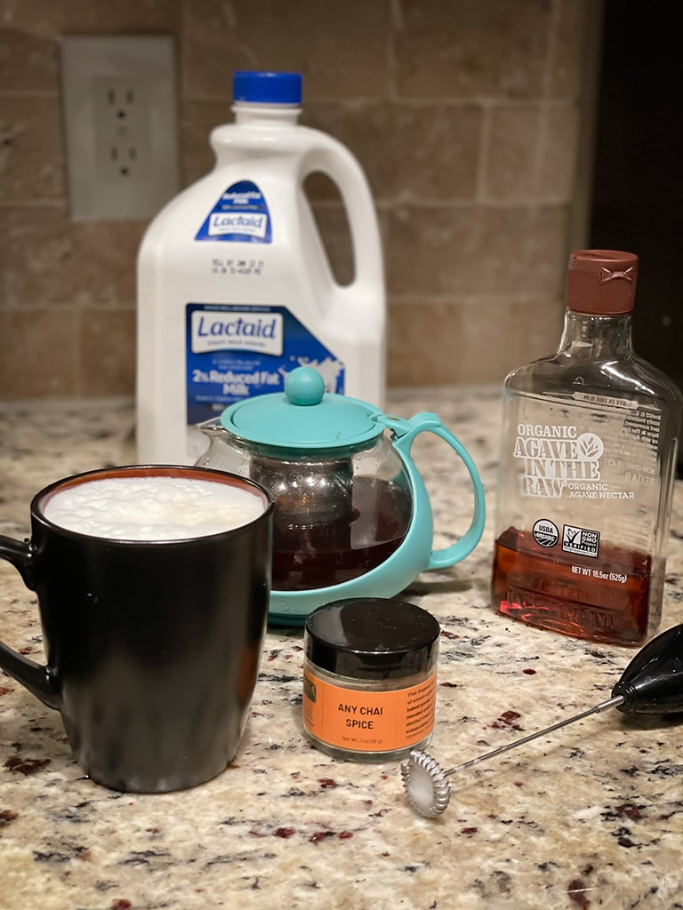 Frother and chai tea ingredients: lactose free milk, Agave in the Raw, Any Chai Spice and a black teacup with hot chai tea in front of a teal teapot steeping black tea.