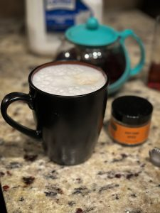 Hot chai tea in black mug with ingredients: Any Chai tea, lactose free milk and raw agave.