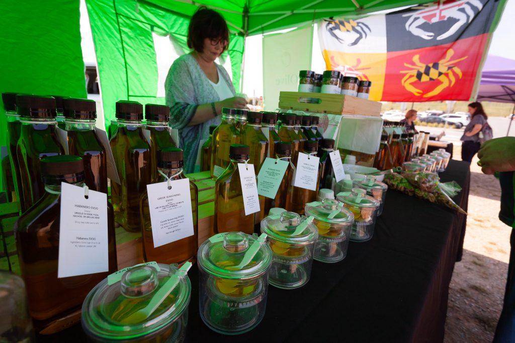 Sherri of Olive & Basket sampling olive oils and spices at Clarksburg Farmers Market.