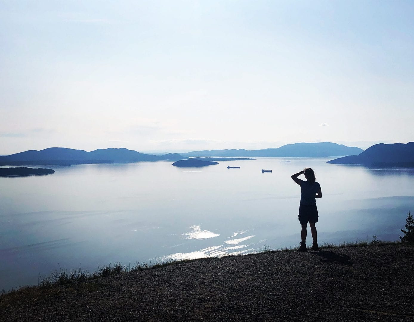 Woman looking into the distance over silver and blue water