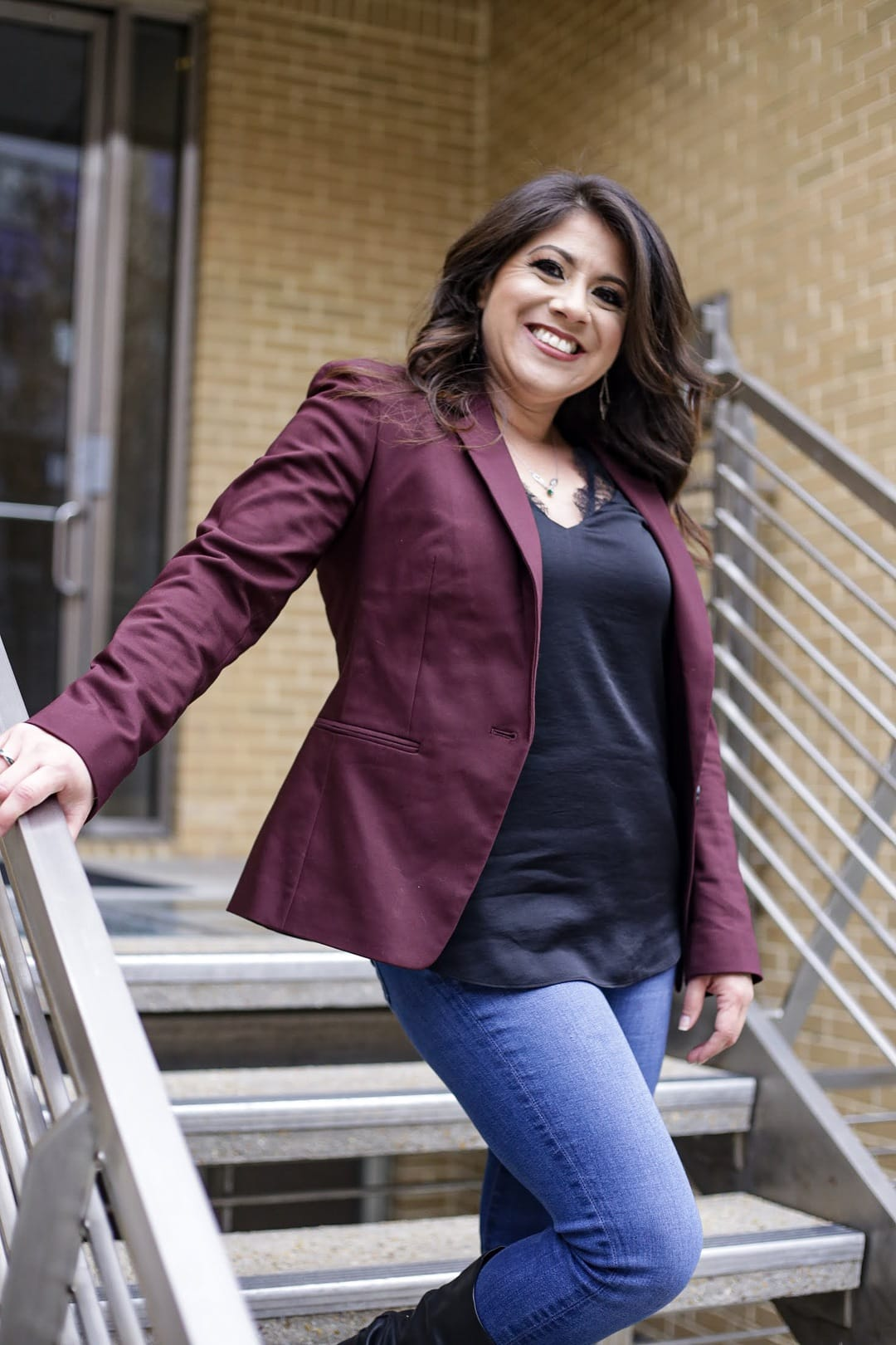 Wendie V standing in jeans, black shirt, and maroon blazer on stairs holding the railing and smiling