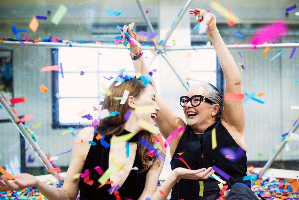 women laughing as rainbow confetti rains down on them