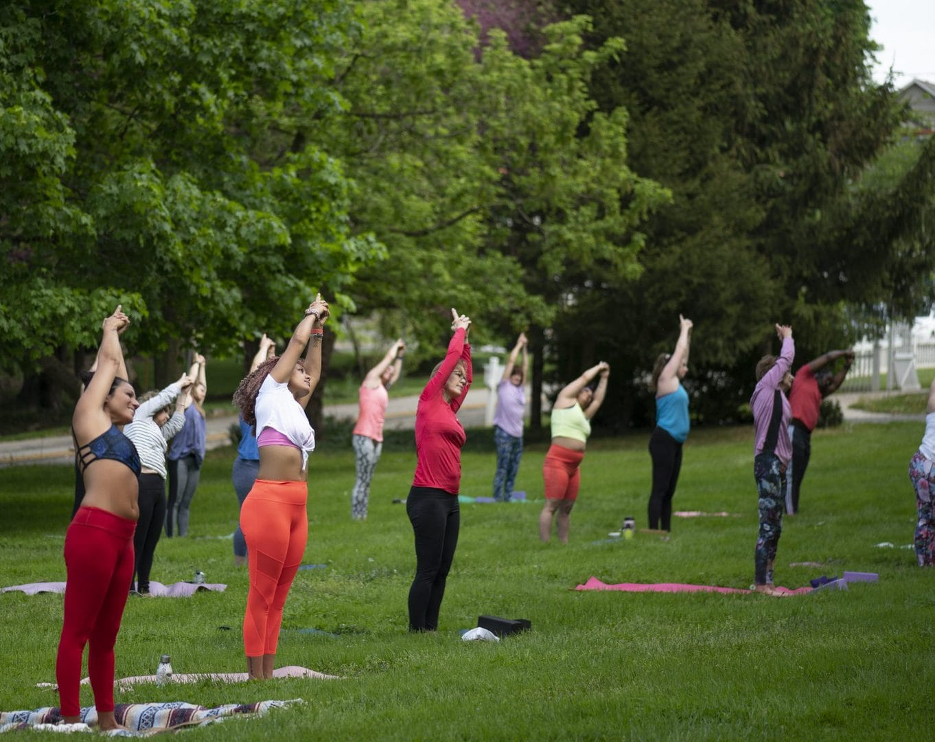 People in multi colored workout clothes doing yoga outside stretching with hands overhead to the right.