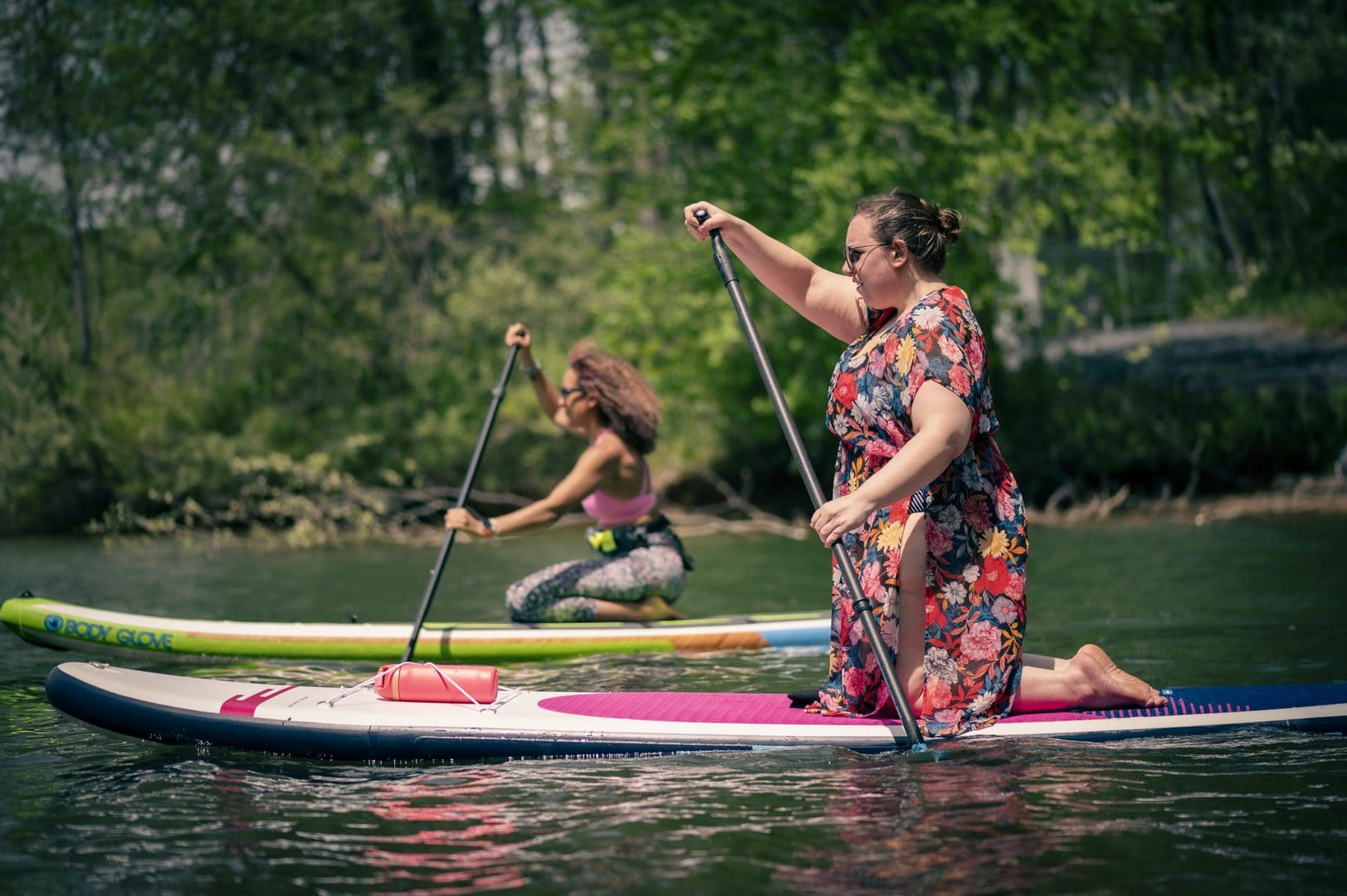 Two women kneeling on paddle boards on a lake