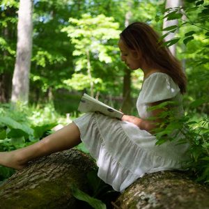 Woman in white dress reading on a fallen tree in the forest