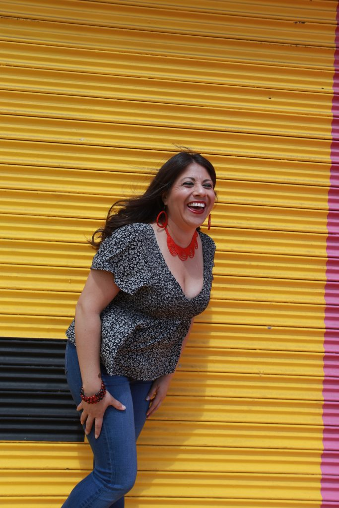 Wellness Grind's Founder Wendie V standing in front of a yellow wall laughing and leaning in
