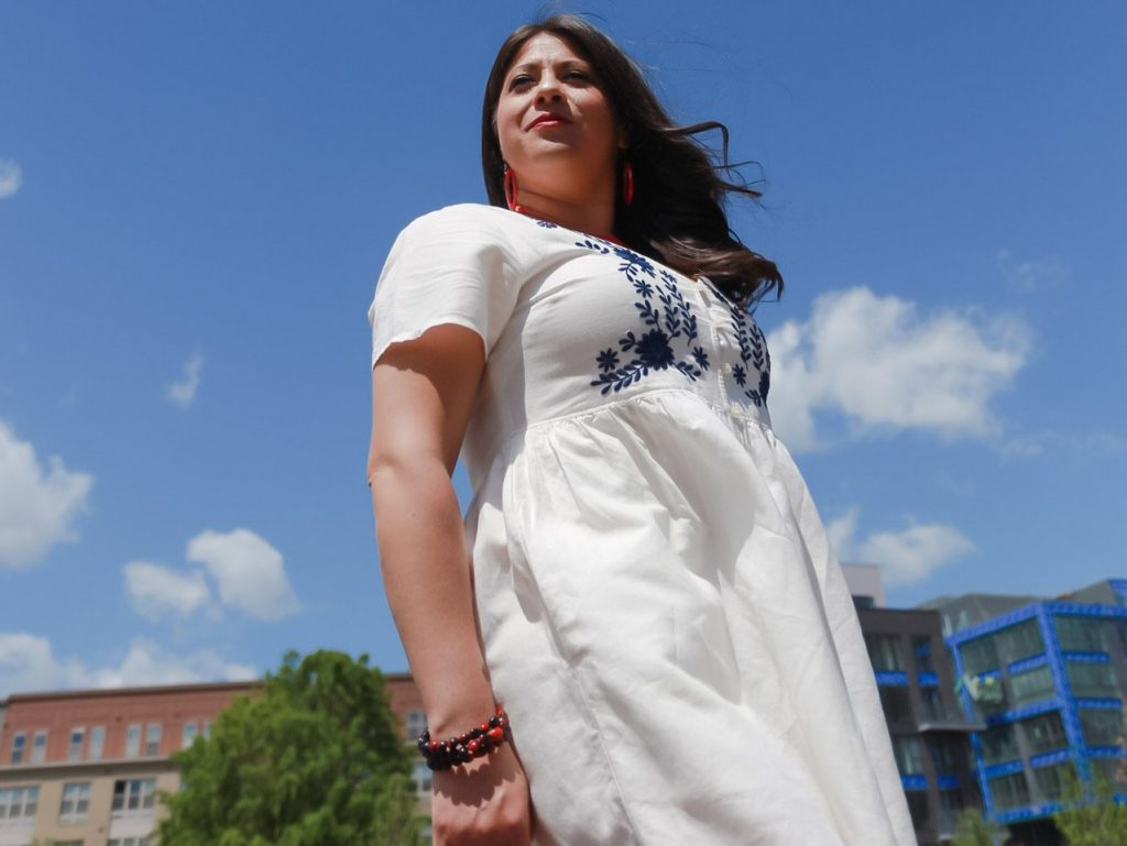 Wendie V. standing proudly in front of a blue sky with white clouds