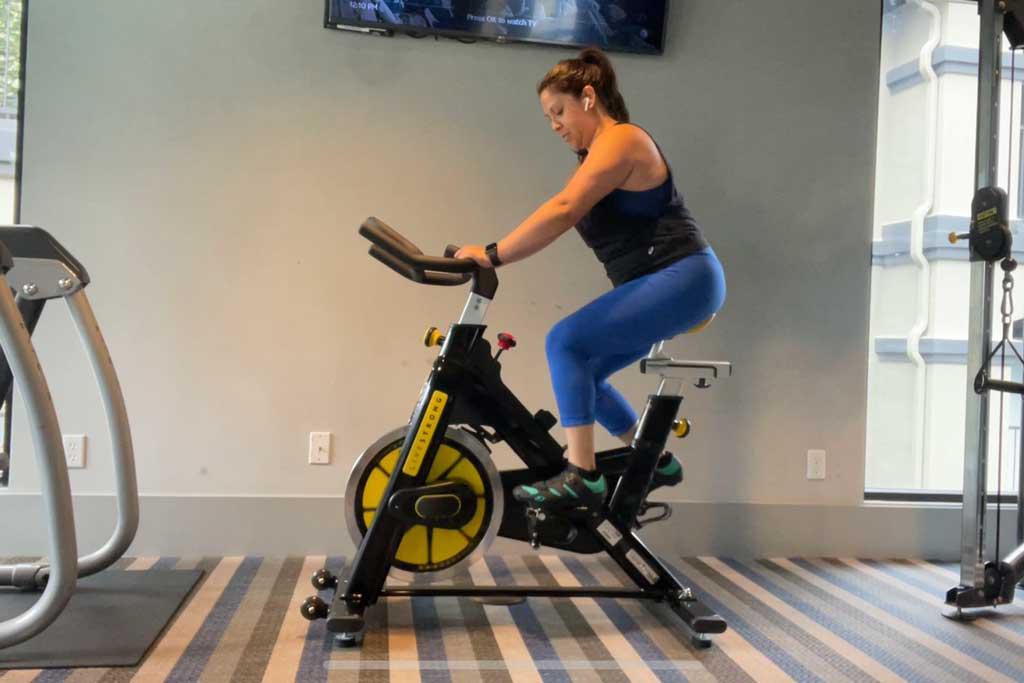 Wendie V on a spin bike with blue pants and a black tank top