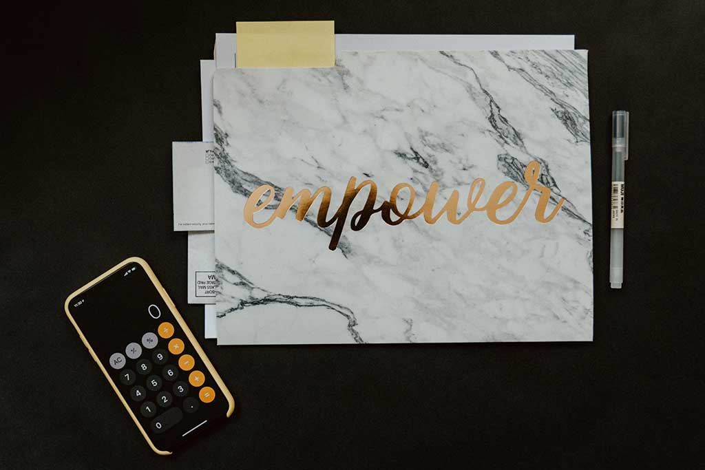 Black background with calculator and marble paper that says empower